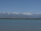 Photo of Issyk-Kul Lake. Kyrgyzstan. Peak Karakol (left, 5216m height) and Peak Oguz-Bashi (right, it was renamed to Eltzin Peak in 2002, height: 5168m).