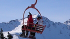 Anton Leshev and Dmitry Leshev are in the chair lift at the background of surrounding mountains of Karakol gorge.